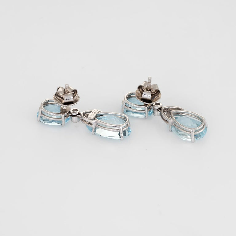 Stylish pair of Suarez aquamarine & diamond drop earrings crafted in 18k white gold.   Aquamarines measure 11mm x 9mm (estimated at 3.50 carats each - 7 carats total estimated weight). The lower pear cut aquamarines measure 15mm x 10mm (estimated at