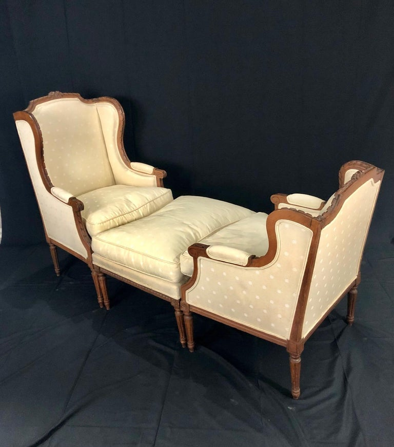 A French Louis XVI style walnut Duchesse Brisée with two bergère chairs and their ottoman from the late 19th century and newer upholstery. This French chaise lounge set features three sections consisting of two bergères of slightly different
