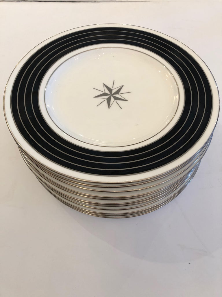 12 handsome Minton china dinner or service plates having contemporary style with black and platinum silver striped borders, white background and a central star decoration.