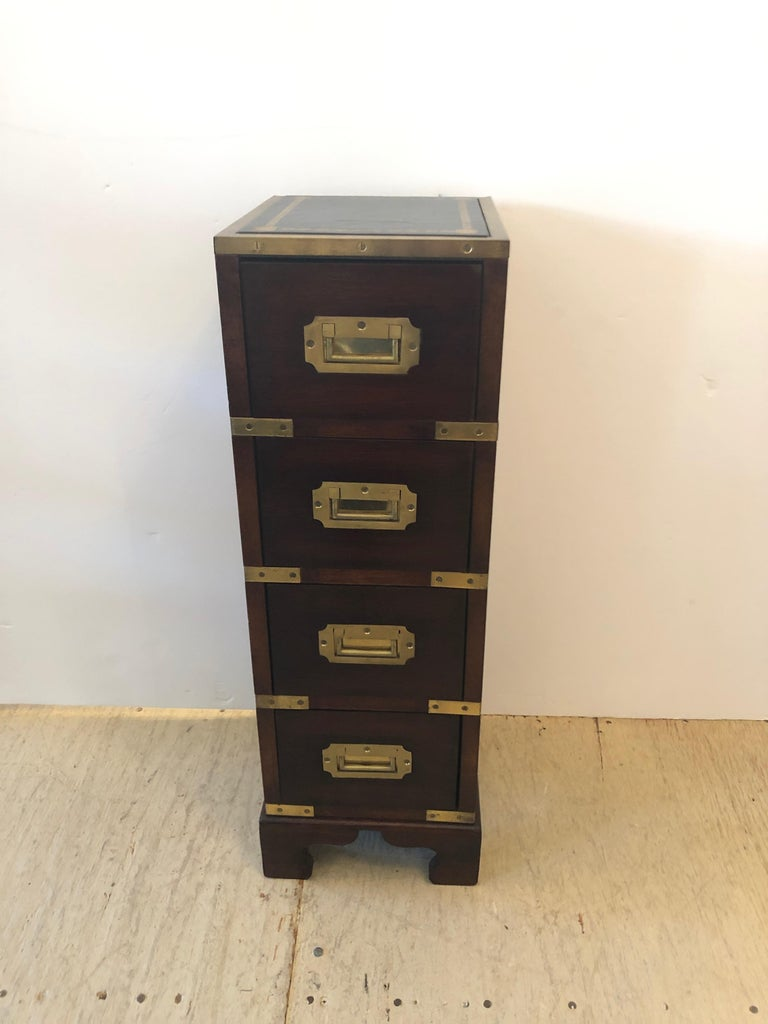 An amazing elegant tall narrow mahogany Campaign chest or side table having 4 stacked drawers with Classic recessed brass hardware and details topped off with a handsome black and gold tooled leather top framed by a brass gallery. A rare jewel in