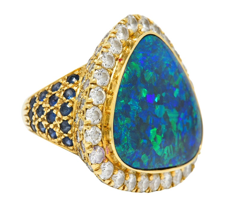 Large cluster ring centers a triangular cushion shaped cabochon of black opal  Opaque with strong green, blue, and violet play-of-color - measures approximately 22.5 x 21.5 mm  Surrounded by round brilliant cut diamonds weighing in total