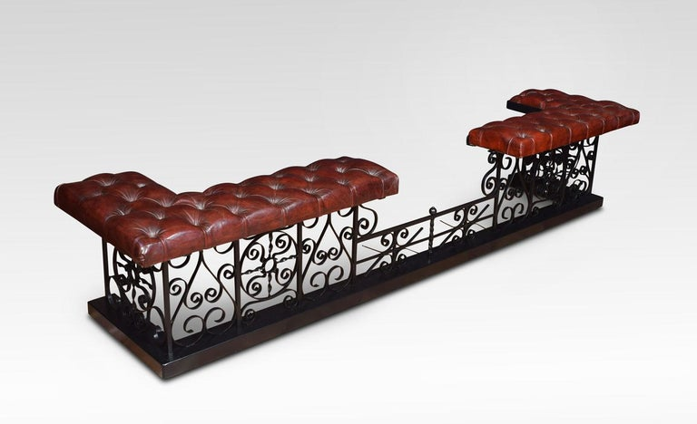 Substantial wrought iron club fender, the deep buttoned leather upholstered padded seats, on square section supports with scrolling decoration. All raised up on plinth base. Dimensions Height 19 Inches External measurements Length 96