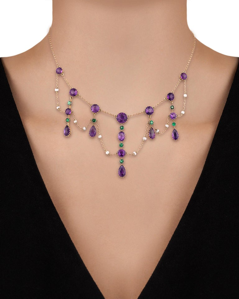 A total of 16 richly colored round and pear-shaped amethysts, nine round demantoid garnets and seed pearls combine to form a colorful garland in this British suffragette collar necklace. Suffragettes wore certain colors synonymous with the movement,