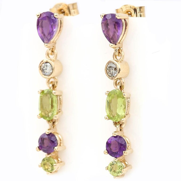 A delightful pair of 9 karat yellow gold Suffragette style drop earrings comprising faceted peridot, amethyst and diamond gemstones. The earrings are set in yellow gold with a chain link to connect the three stones, with a peg and butterfly fitting.