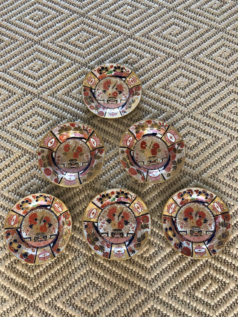 This suite is of two bowls and four plates early 19th century Chamberlain's Worcester Porcelain dishes, circa 1804, decorated in underglaze blue and having enamel red and gold in the Imari style marked in purple thinking this is early Nelson Pattern.
