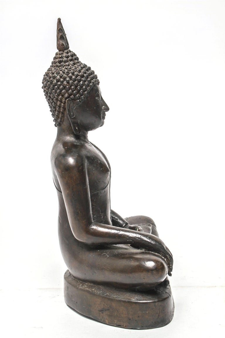 Sukothai style Thai patinated bronze seated Buddha sculpture with downcast eyes, flaming ushnisha, and elongated ears, depicted in Bhumisparsha mudra. The piece is in great vintage condition with a desirable age-appropriate patina.