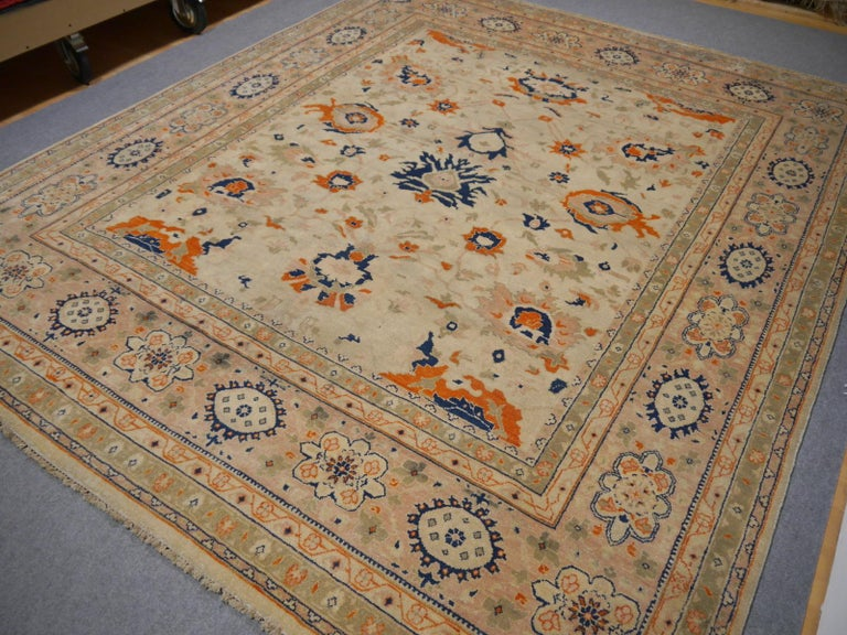 A beautiful circ 8 x 10 ft contemporary design carpet, hand knotted using finest wool. On a light crème field, the design of Lotus blossoms standing next to each other executed in orange, blue and green tones.