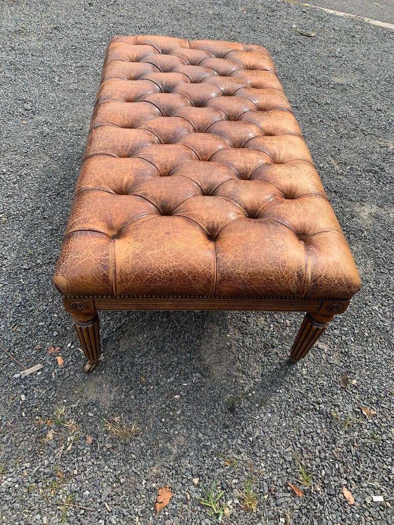 A hard to find handsome English 19th century tufted leather ottoman with brass nailhead details. The carved mahogany base includes reeded tapered legs that terminate in brass casters.