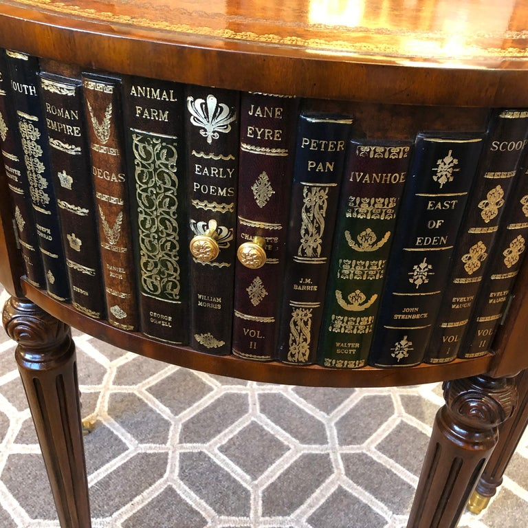 Handsome leather wrapped center table or side table having tooled leather top and trompe l'oeil books around the periphery. There are 3 sets of double doors that open to storage, and 3 sets of 2 drawers. Mahogany legs are carved and terminate in