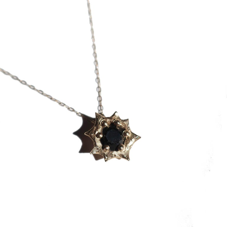 Hand carved sun cast in 14K yellow gold featuring a 1 carat Black Diamond. This pendant has a total diameter of 10mm and is a wonderful stacking piece. This is strung on a 16 inch 14k gold chain. Please note black diamonds contain fractures that