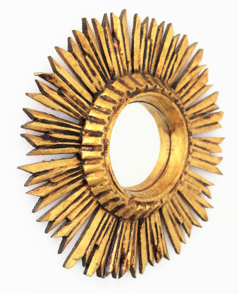Mini sized carved giltwood convex sunburst mirror, France, 1940s This lovely French petite giltwood sunburst mirror with convex glass has a beautiful patina. Place it alone or as a part of a sunburst mirrors wall composition with other mirrors in