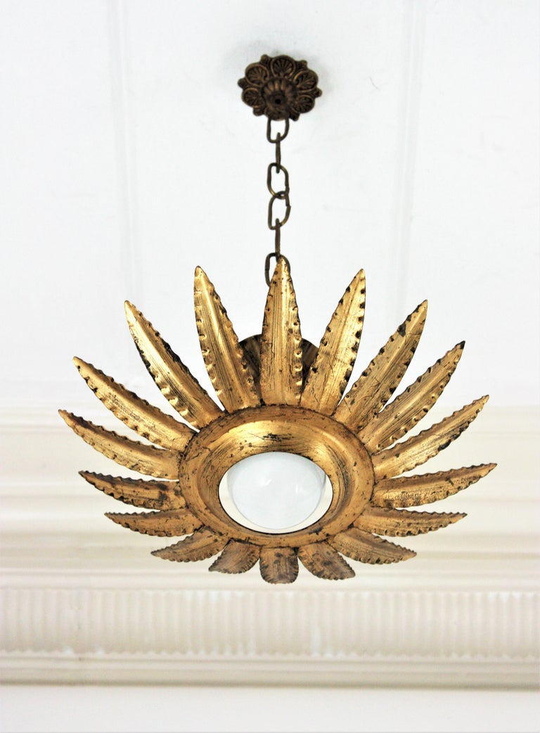 Eye-catching gilt wrought iron sunburst or flower shaped ceiling light fixture, wall sconce or pendant, Spain, 1960s.