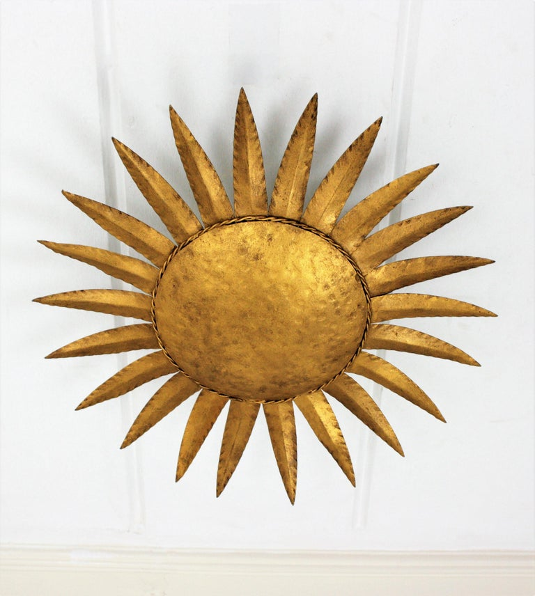 Eye-catching hand-hammered sunburst ceiling flushmount in the style of Brutalism. Manufactured by Ferro Art, Spain, 1960s. This wrought iron gilded sunburst flush mount or wall sconce will be a nice midcentury Brutalist accent wherever you place