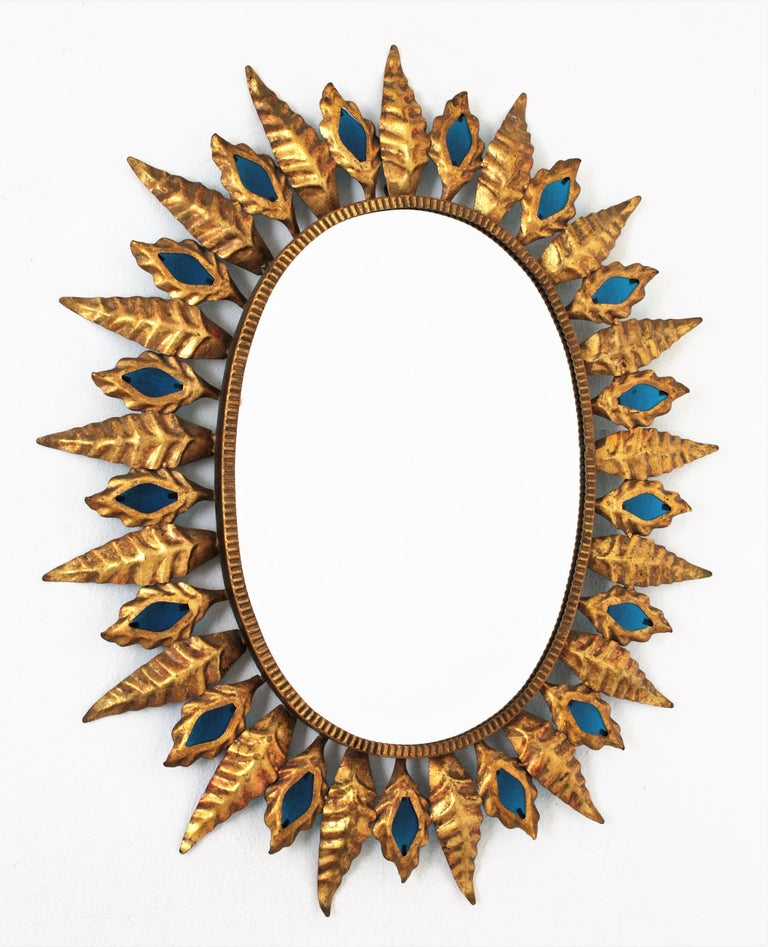 Blue glass and gilt metal oval sunburst mirror in the Hollywood Regency style, Spain, 1960s. This oval sunburst mirror features a leafed frame with alternating large and small leaves accented by Classic blue glasses. Blue is the color of the year