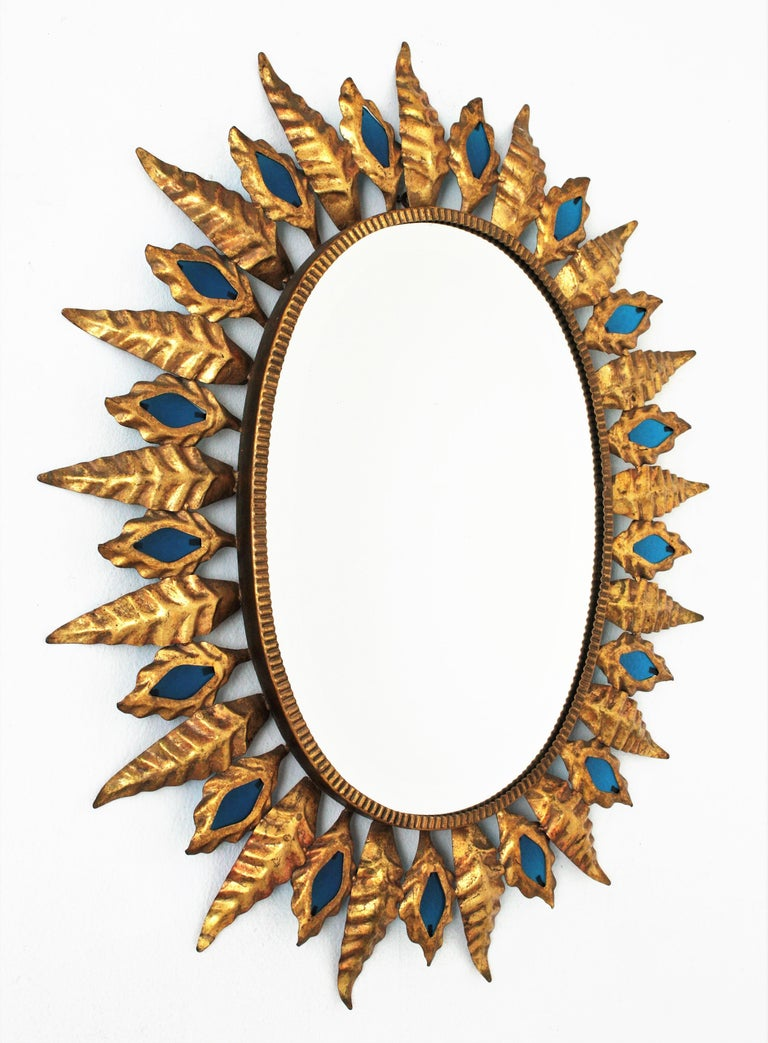 Spanish Sunburst Gilt Iron Oval Mirror with Blue Glasses in the Hollywood Regency Style For Sale
