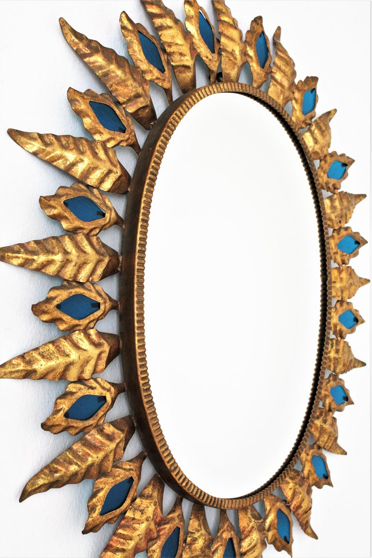 Sunburst Gilt Iron Oval Mirror with Blue Glasses in the Hollywood Regency Style In Excellent Condition For Sale In Barcelona, ES
