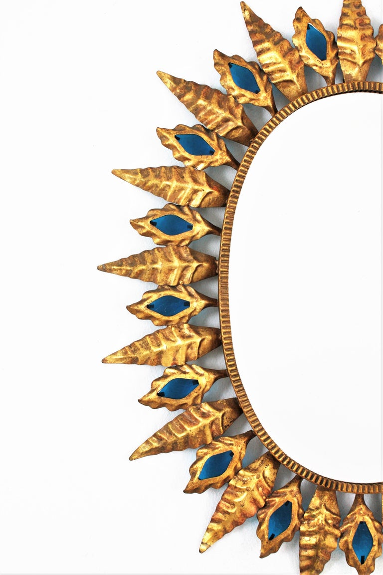 Sunburst Gilt Iron Oval Mirror with Blue Glasses in the Hollywood Regency Style For Sale 1