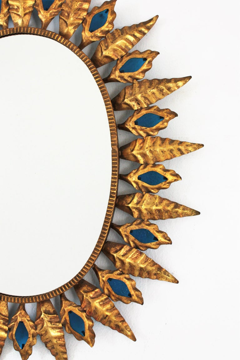 Sunburst Gilt Iron Oval Mirror with Blue Glasses in the Hollywood Regency Style For Sale 2