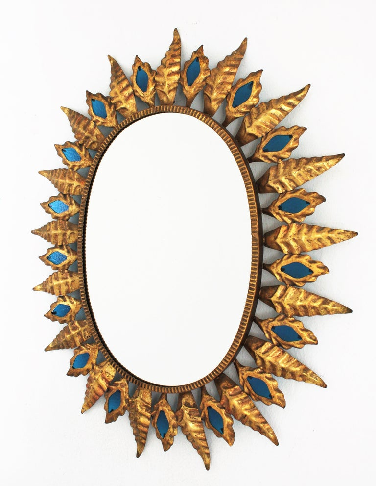 Sunburst Gilt Iron Oval Mirror with Blue Glasses in the Hollywood Regency Style For Sale 4