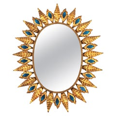 Sunburst Gilt Iron Oval Mirror with Blue Glasses in the Hollywood Regency Style