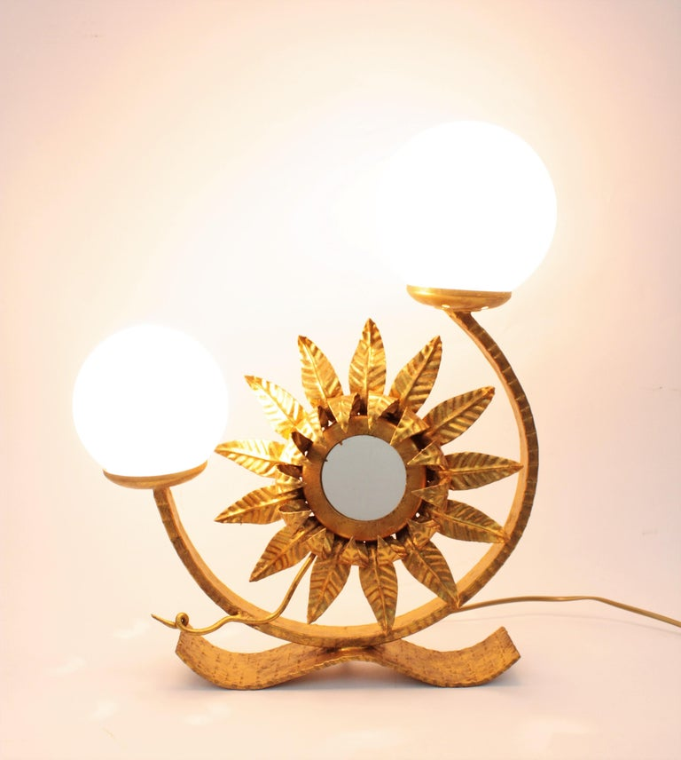 Wrought iron Spanish two-light table lamp with opaline glass globe shades and decorative sunburst mirror. This eye-catching table lamp with a sunflower or sunburst mirror between the lights. Outstanding naturalistic design with Hollywood Regency