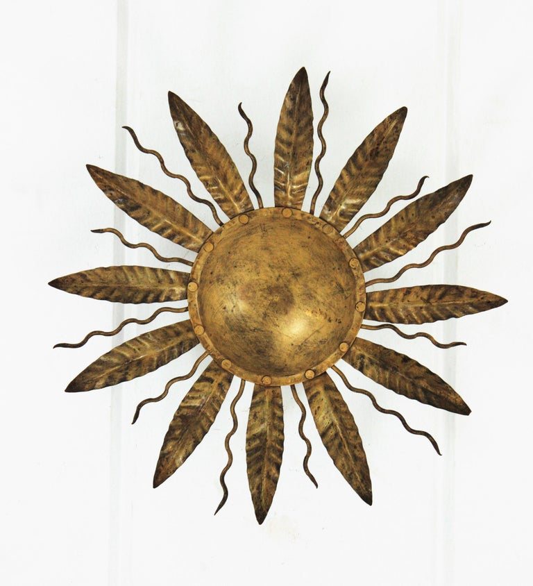 Lovely gilt metal leafed sunburst flushmount. Spain, 1950s-1960s. This ceiling flushmount features an iron structure with a central round panel surrounded by alternating leaves and curly rays. It has a nice aged patina. Two E14 bulbs at the back