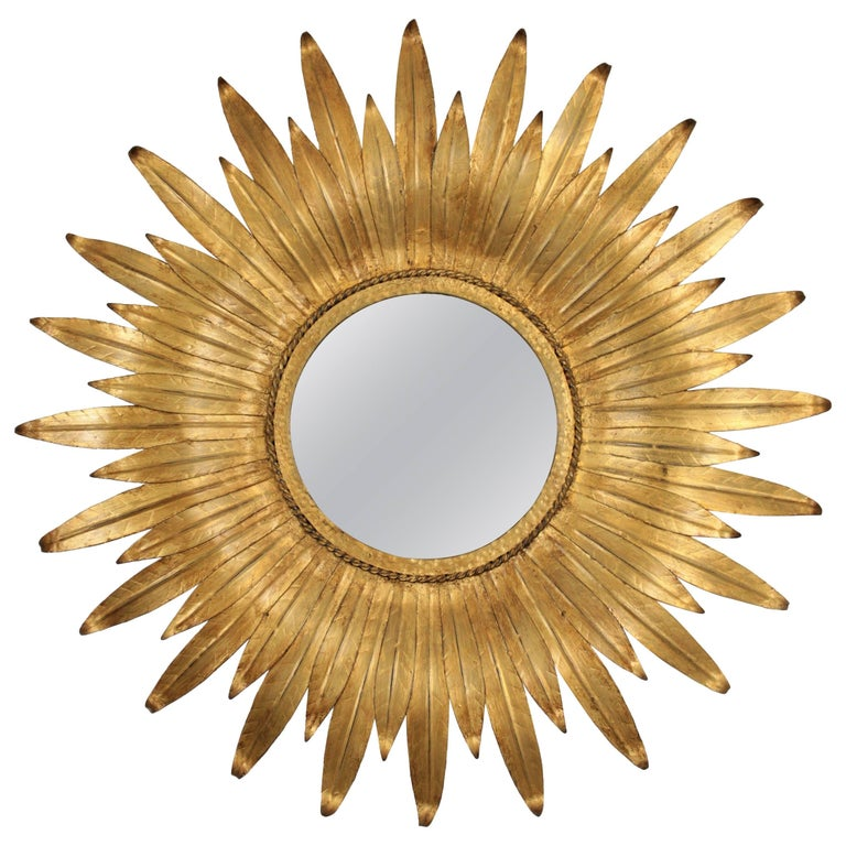 A lovely sunburst flower shaped mirror gilt metal sunburst mirror, Spain, 1950-1960. This wall sunburst mirror features a circular glass framed with curved gilt leaves in two sizes. Beautifully handcrafted. It has a nice aged patina. This mirror