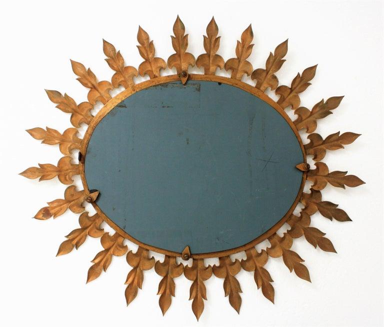 Sunburst Oval Wall Mirror with Fleur de Lys Frame in Gilt Iron For Sale 4