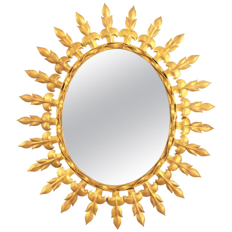 Spanish modernist oval shaped gilt iron sunburst mirror, Spain, 1950s The frame is comprised by alternating leaves or Fleur de Lys motifs joined between them by a twisted strip. Lovely to be placed alone and also as a part of a wall composition