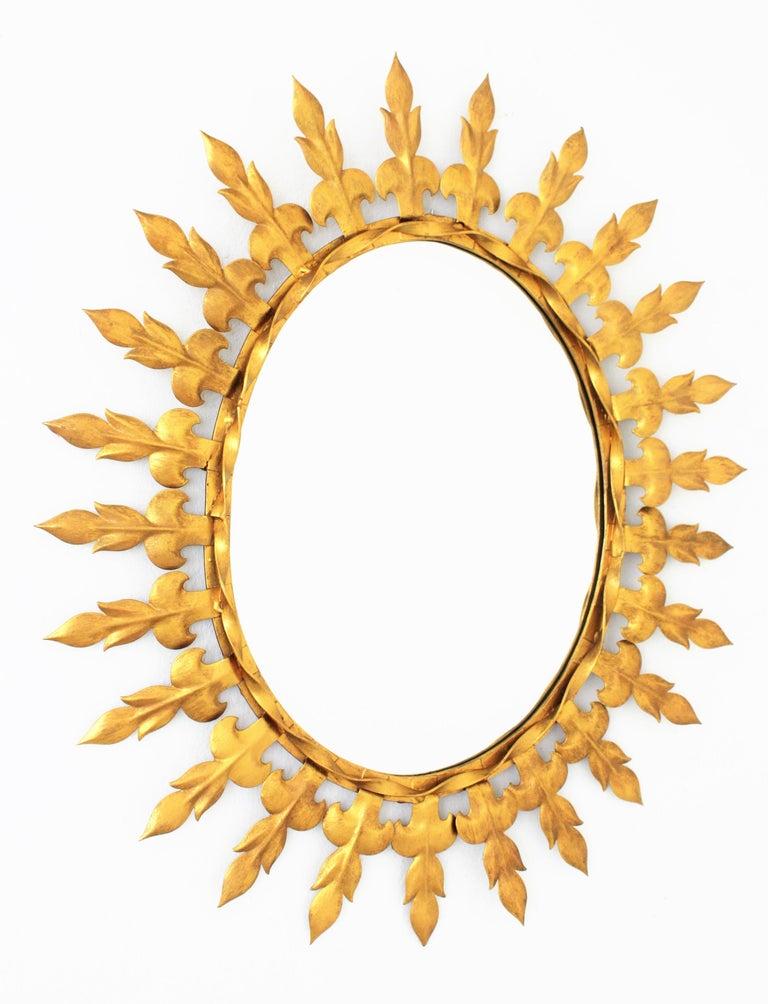 Mid-Century Modern Sunburst Oval Wall Mirror with Fleur de Lys Frame in Gilt Iron For Sale