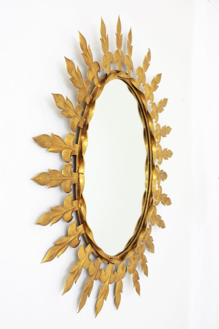 Spanish Sunburst Oval Wall Mirror with Fleur de Lys Frame in Gilt Iron For Sale