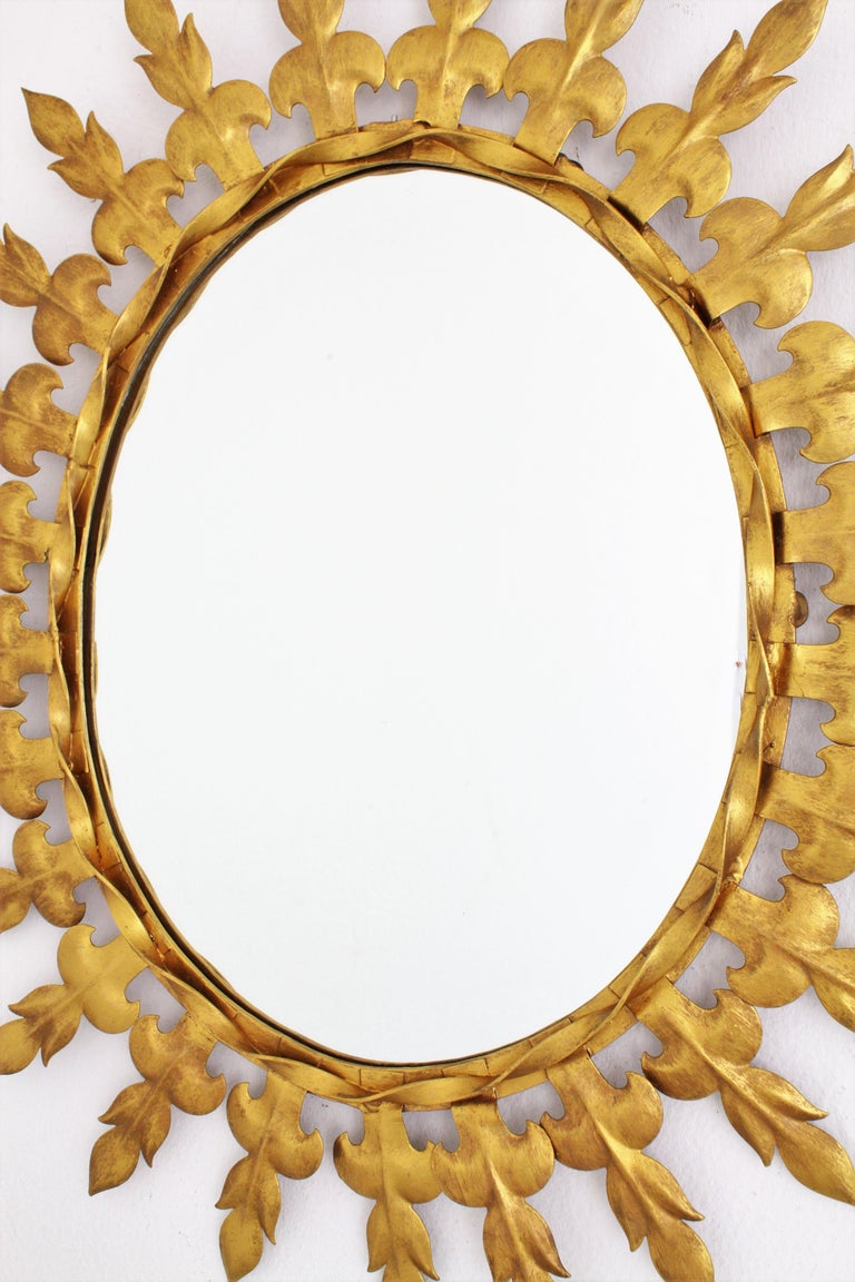 Mid-20th Century Sunburst Oval Wall Mirror with Fleur de Lys Frame in Gilt Iron For Sale