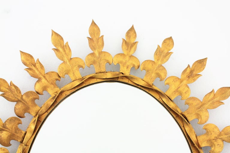 Metal Sunburst Oval Wall Mirror with Fleur de Lys Frame in Gilt Iron For Sale