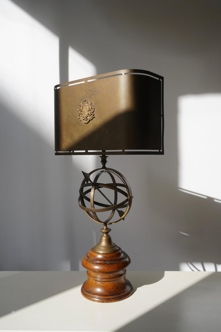 Vintage table lamp with a wooden base and centre in solid brass with a sundial. The shade which is original is also made of patinated brass. Has room for two standard E27 bulbs. Gives a warm glow when lit. Measures: Height 65 cm. Width 36