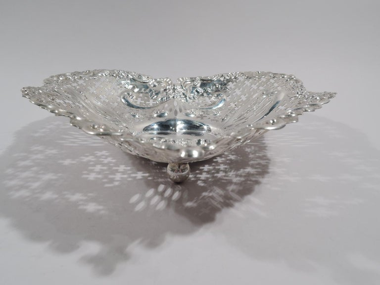 Super big and super romantic turn-of-the-century sterling silver heart bowl. Made by Gorham in Providence. Solid well; curved and tapering sides with chased scrolls and ribbon bows, and pierced geometric ornament. Irregular rim with scrolls, leaves,
