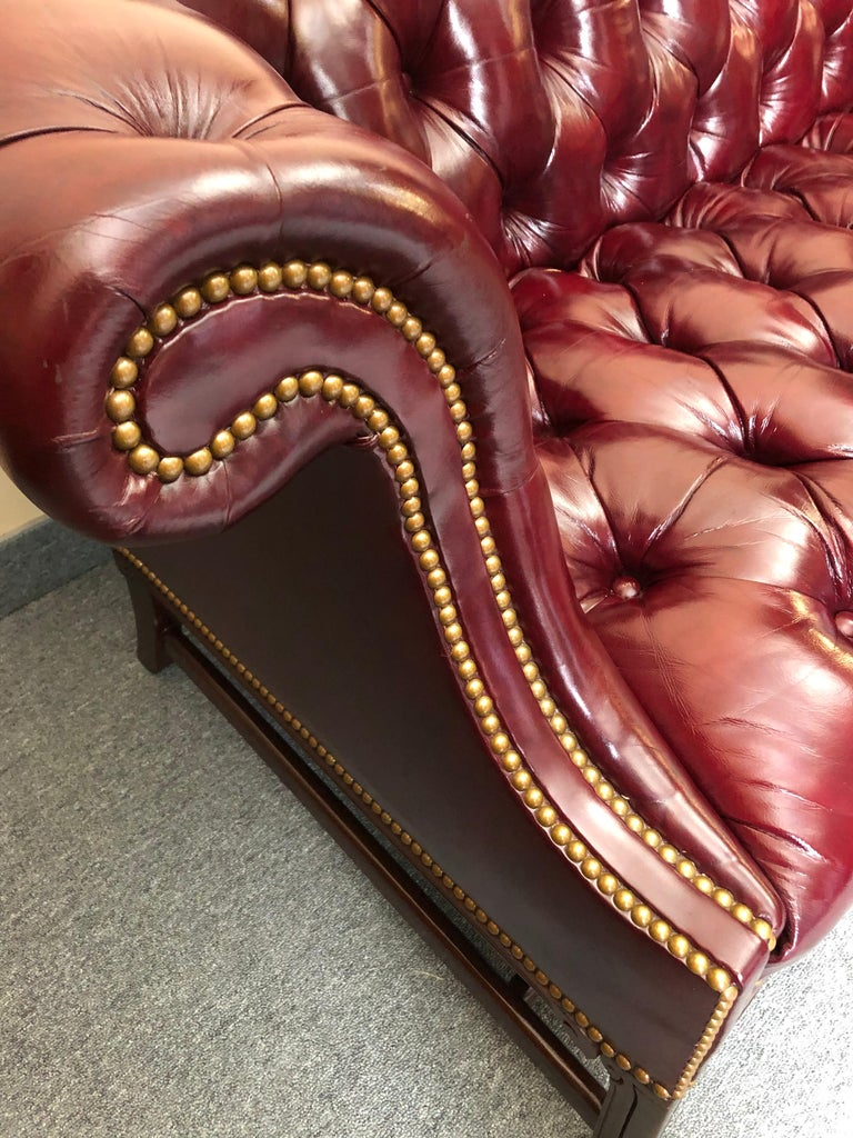 Sumptuous traditional camelback Chesterfield style sofa having supple rich deep maroon tufted leather, brass nailhead detailing, and mahogany legs. Very comfortable and Classic.