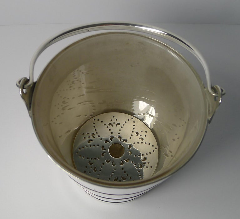 A wonderful antique English silver plated ice pail in the form of coopered wooden bucket with swing handle.  What makes this example particularly special is the original hand blown glass liner, rarely do they have a liner. There is also a silver