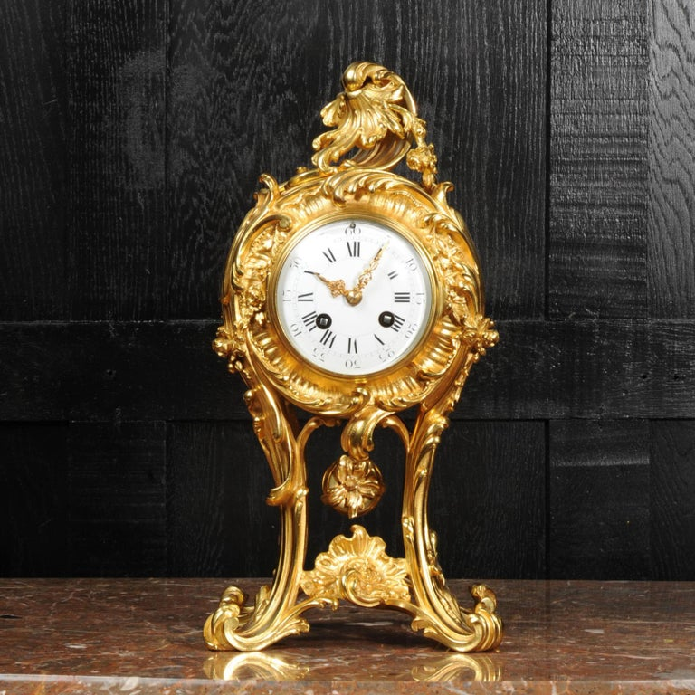 A stunning antique French clock, circa 1870, finely modelled in ormolu (finely gilded bronze). It is a beautiful Rococo balloon shape with boldly flamboyant acanthus legs hold the movement aloft. The original ormolu pendulum swings gently below.