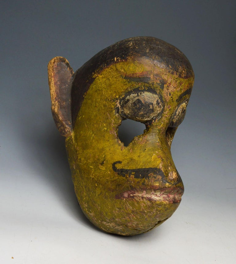 Nepalese temple festival mask of Hanuman the Monkey God A superb very old temple/festival mask of Hanuman the monkey god The smiling monkey god with protruding snout large ears curling mustache  Ancient layered patina with remains of pigments from