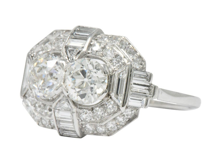 Centering 2 old European cut diamonds, weighing approximately 0.85 and 0.90 carat respectively, HIJ color and VS clarity  Accented by triangular, trapezoid, baguette, and single cut diamonds, weighing approximately 1.75 carats total, GHI color and