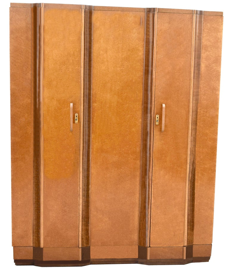 Superb and totally original is this 1930s Art Deco triple door wardrobe with working key. Not only does this wardrobe look impressive with it's blonde maple veneers and Walnut banding which match and follow on each door but it's extremely generous