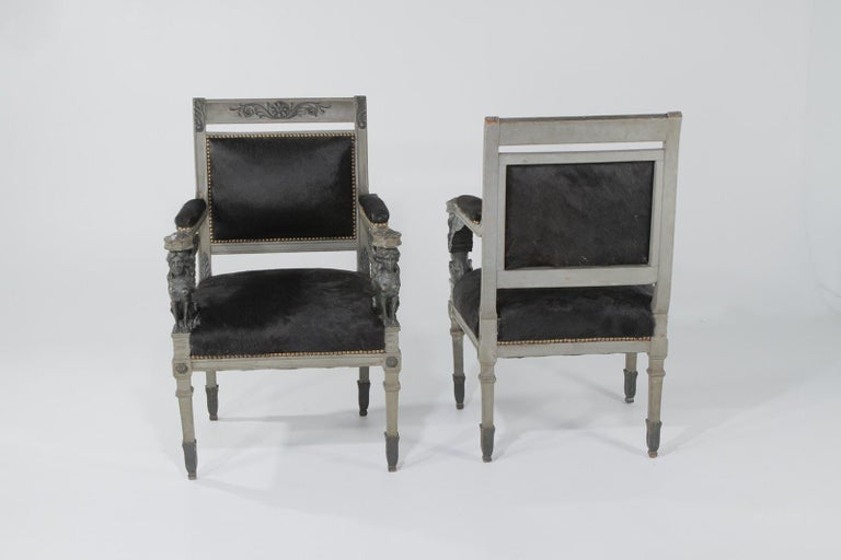 Truly amazing ornately carved wood Egyptian Revival armchairs having a gilded underpaint with grey wash paint, glamorous details including rosettes and female sphinx figures on the arms, and glamorously contemporized with black cowhide upholstery.
