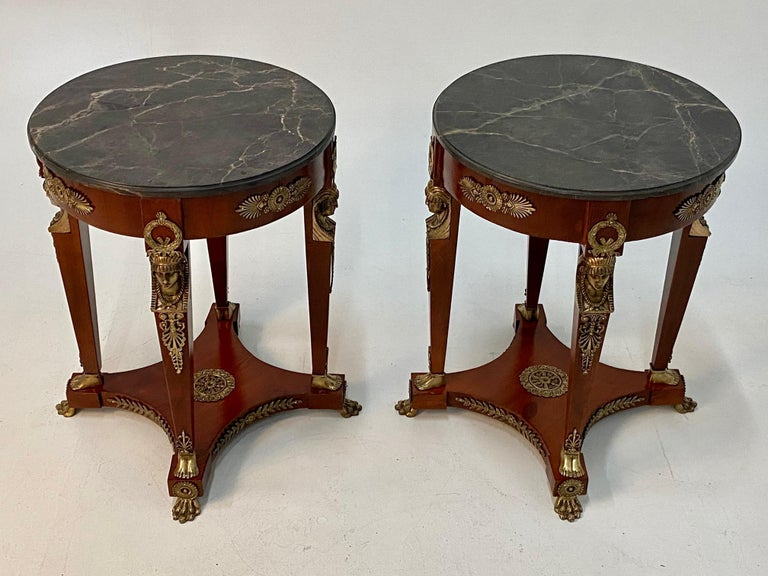 Elegant and ornate pair of round French Empire style end tables having rich mahogany bases with 4 legs and fancy bronze figural decoration at the tops of the legs, wreaths, and animal paw feet on elevated bases. The black and grey veined marble tops