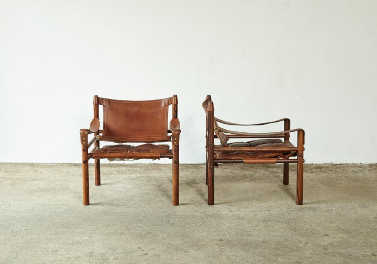 A super pair of authentic vintage Arne Norell safari sirocco chairs in wonderfully grained rosewood and heavily patinated brown leather. Made by Norell Mobler in Sweden, 1970s.  The chairs will need to be disassembled for shipping but were