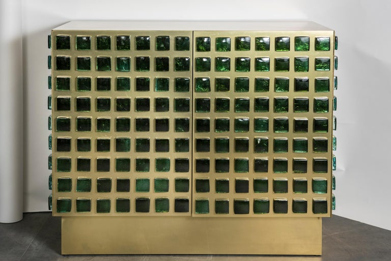 This pair of cabinets are in wood covered with brass, and decorated with molted green glass squares. Unique and contemporary creation by Studio Glustin, France, 2019.