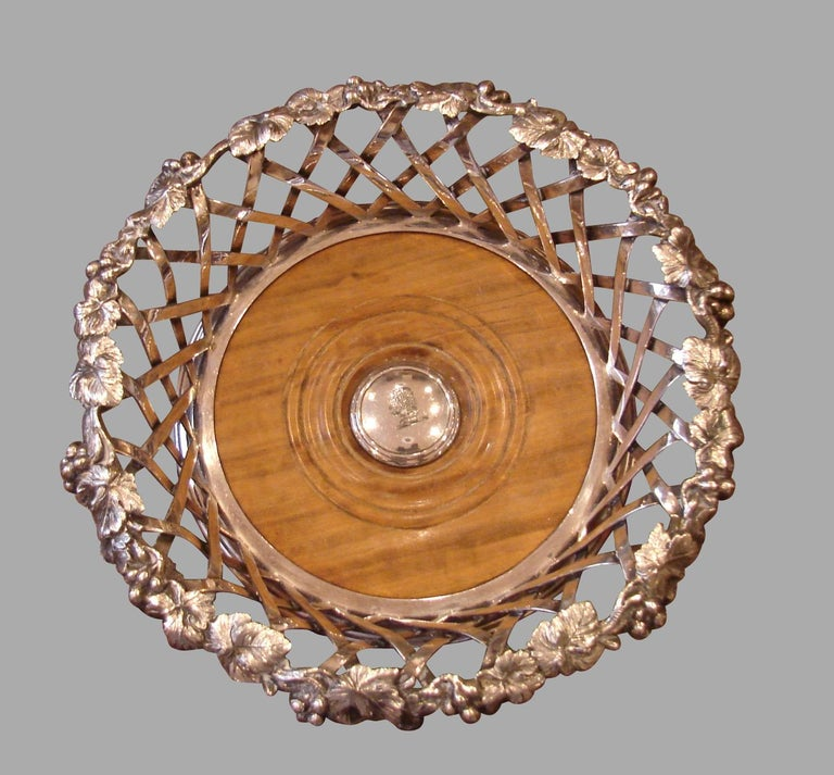 A superb and elegant pair of Elkington and Company silverplate decanter coasters of large scale, each with a foliate vine and grape decorated rim, above a lattice designed side, framing turned walnut bases with central bosses engraved with an