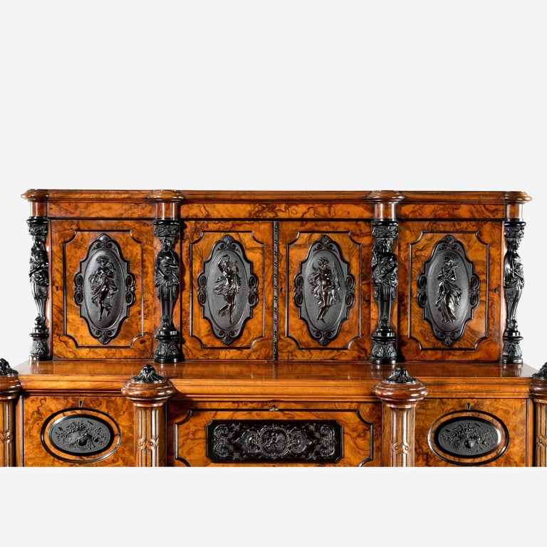 A superb quality burr walnut cabinet of upright rectangular form with three small drawers disguised in a frieze above three glazed cupboards between pilasters, the upper section comprising four smaller cupboards applied with black cartouches showing