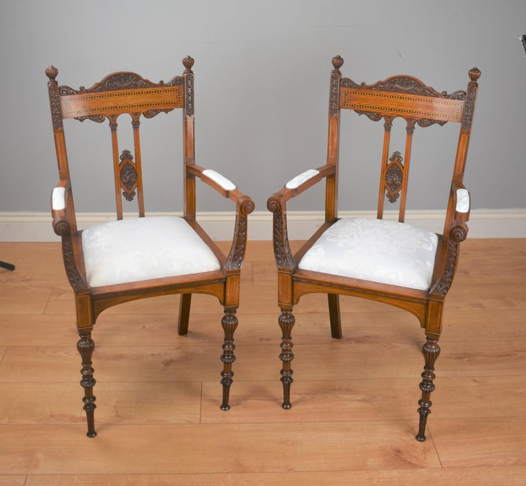 A pair of Victorian inlaid mahogany chairs of exhibition quality attributed to James Shoolbred, a good example of fine hand carving, the seats are upholstered in a white patterened material.  Dimensions:  Width 20