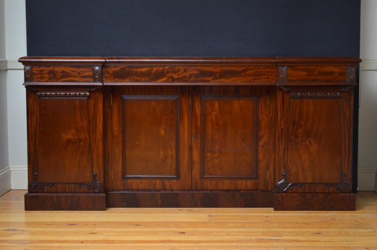 R00 Fine quality and very elegant William IV breakfronted sideboard in mahogany, having figured mahogany top above 3 oak lined drawers and flamed mahogany cupboard doors enclosing a shelf, all flanked by further panelled and carved cabinet doors