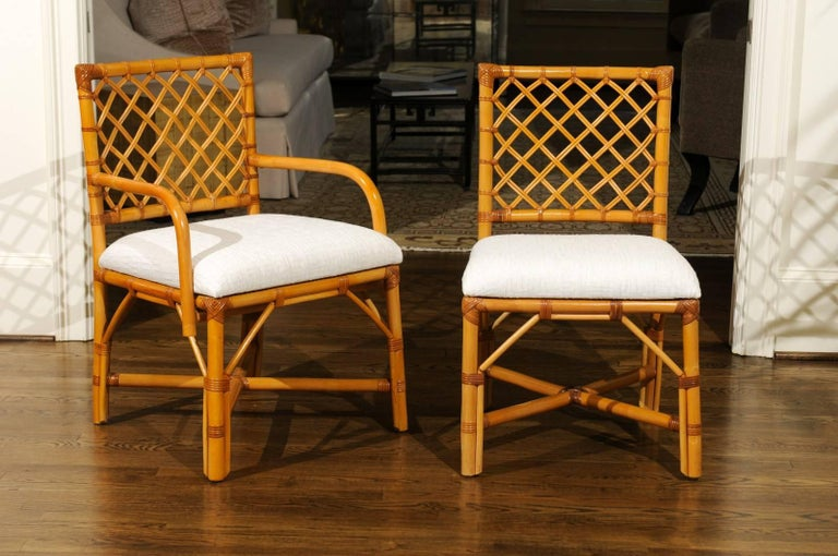 A beautiful set of eight (8) vintage dining chairs, circa 1975. There are two (2) host and six (6) side chairs. Expertly crafted rattan and hardwood construction with a lovely woven lattice back detail - mellowed to absolute perfection. Stout,